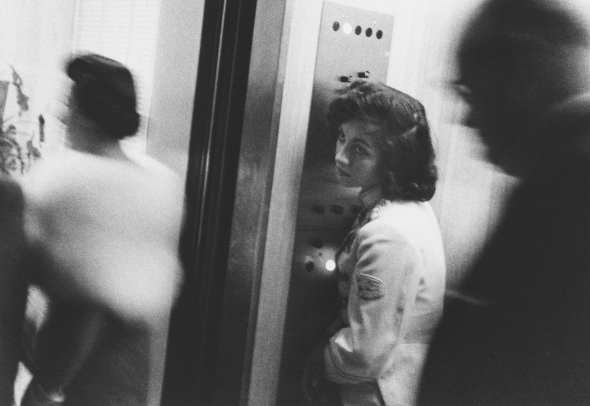 Robert Frank. This is an image made with a hand camera, and it reveals interesting facts about exposure by the way that space is described in the frame. The elevator operator is relatively still, but people around her are blurred, leading us to recognize that the photographer was also still and used a shutter speed that was relatively slow (1/15 to 1/30th of a second?). The depth of field is relatively narrow, so a wider (smaller number) aperture was used.