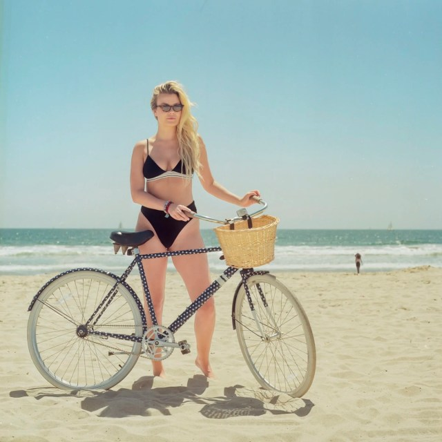A portrait of a woman with her bike on the beach