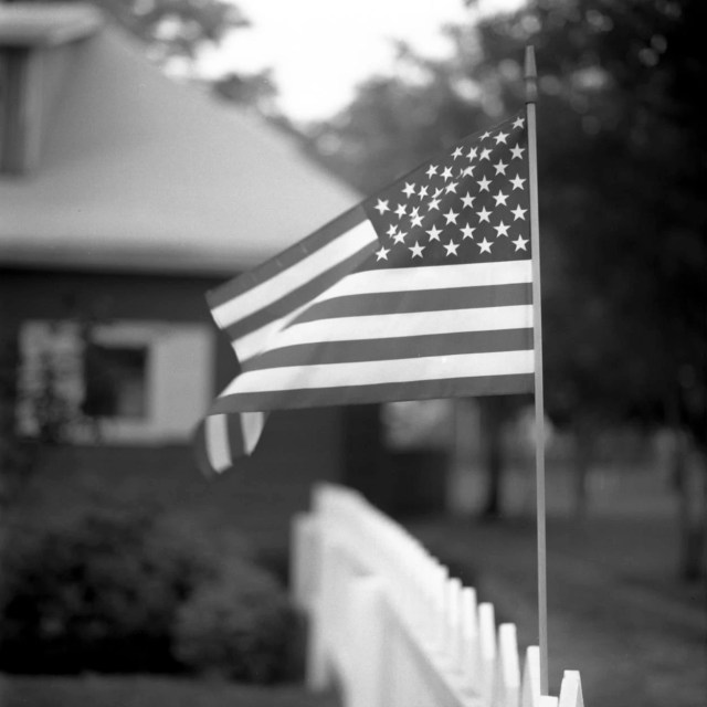 The American flag on the fence of an old house
