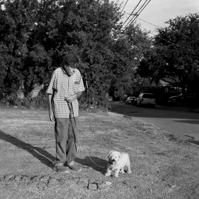 A man walking his dog outside of his home in Old East Dallas