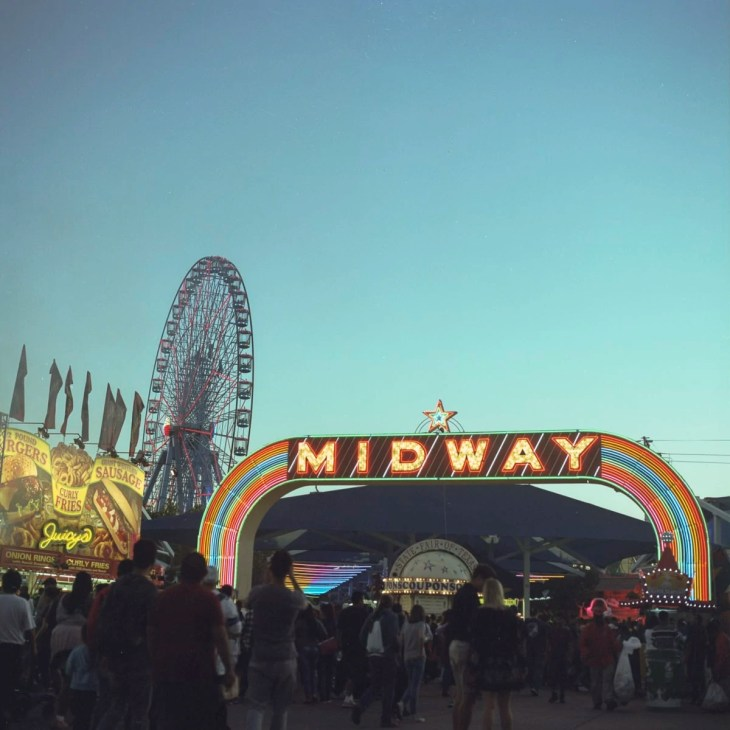 The Midway sign lit up in the evening