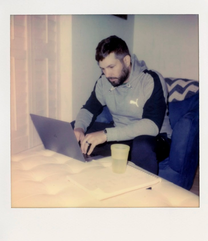 Me working remotely using the ottoman as desk