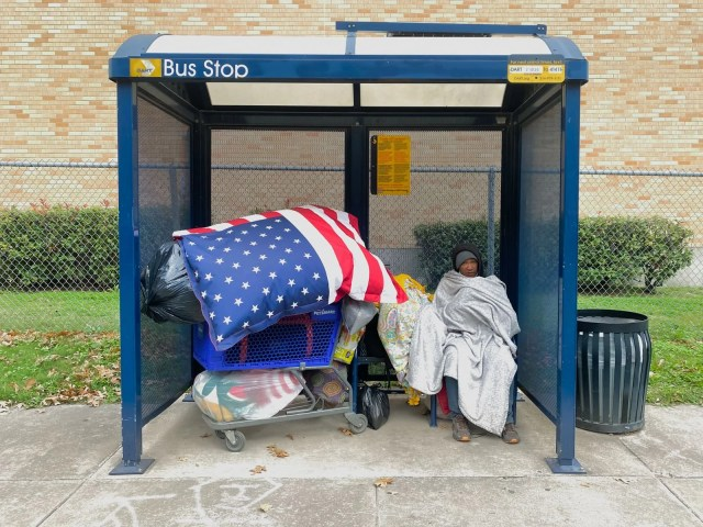 A homeless woman with an American Flag comforter in Dallas, Texas