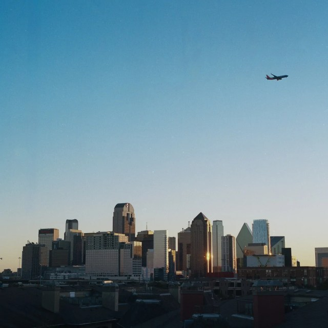 A plane flying over the Dallas skyline