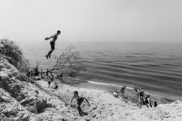 A boy jumping off of a sand dune at Lake Michigan beach in Holland, Michigan