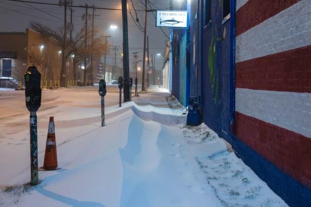 Snow piled up on the sidewalk in Deep Ellum