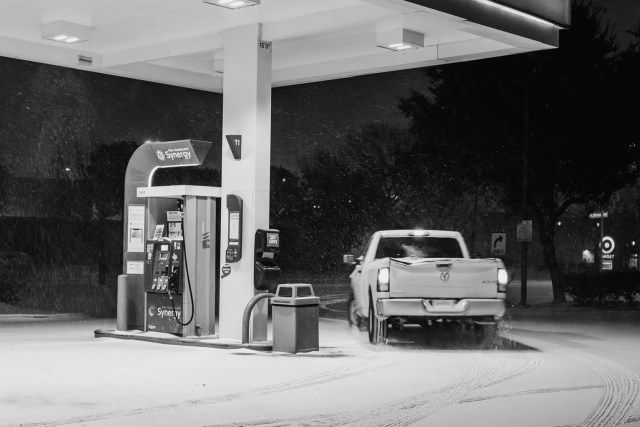 A pickup truck leaving the gas station at night in a snowstorm