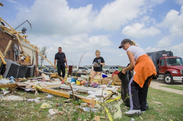A family cleaning up tornado debris after their home was hit