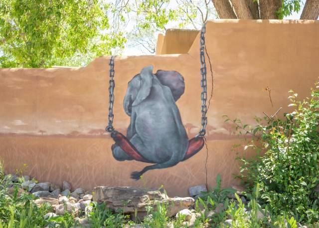 A mural of an elephant on a swing in Santa Fe