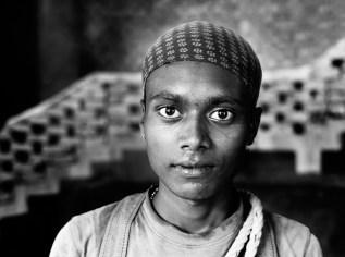 Prem Ghosh a 20 ans et vient du Bengal. Il ne connait pas le nom de l'endroit (ville, village) d'ou il vient. Cela fait un mois qu'il habite au village et travaille sur le chantier ou il s'occupe des échafaudages et de tout types de travaux a faire en hauteur. A propos de cette photo, il en est très heureux et préfère de loin la version en noir et blanc.