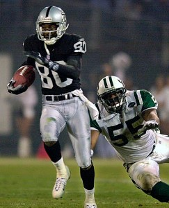 Oakland Raiders' Jerry Rice (80) makes a 47-yard catch and run in the third quarter as New York Jets' Marvin Jones attempts to stop him during the AFC Wildcard playoff game in Oakland, Calif., Saturday, Jan. 12, 2002. The Raiders beat the Jets, 38-24.  (AP Photo/Bob Galbraith)