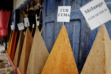 spices in the shape of pyramids with a blue door behind them