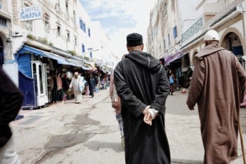 a Moroccan man in traditional dress on a shop-lined street
