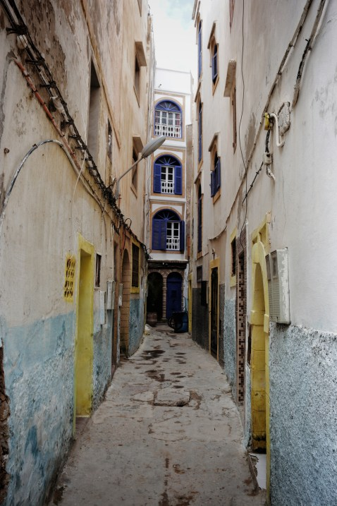 a long, empty, colorful alley leading to a door