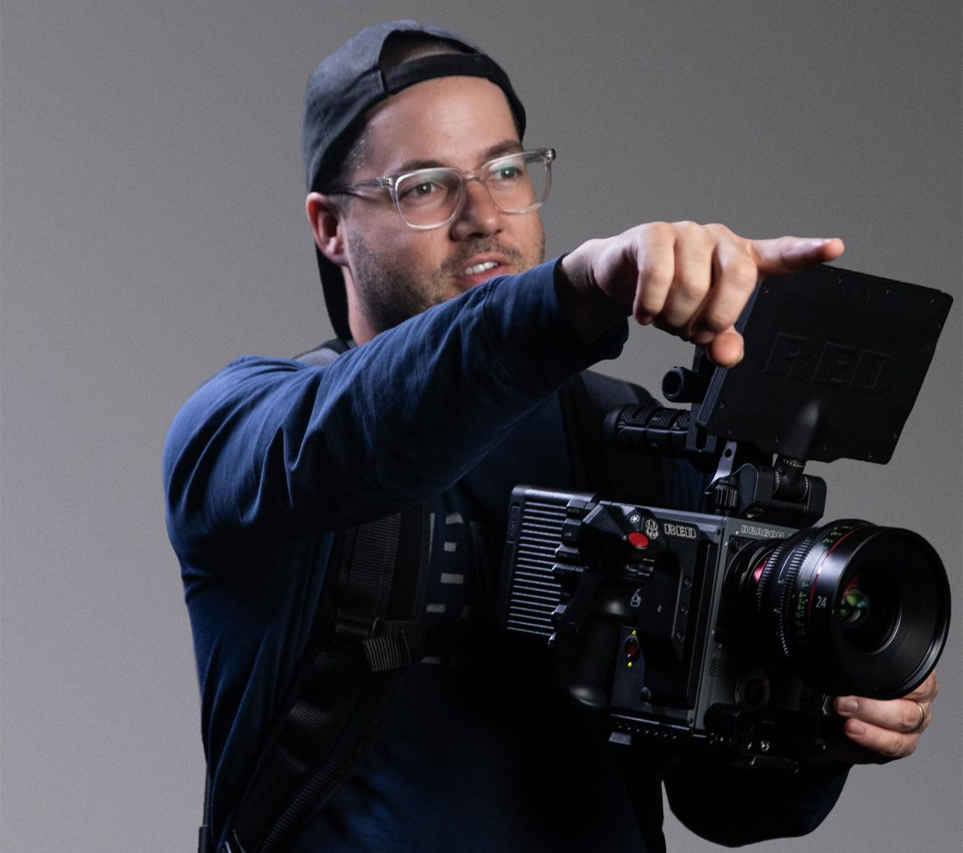 Matt holding a camera and pointing at something important
