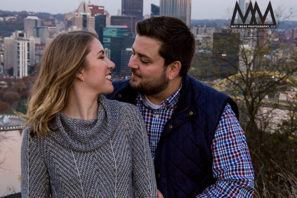 engaged couple smiling at each other in front of Pittsburgh, PA skyline