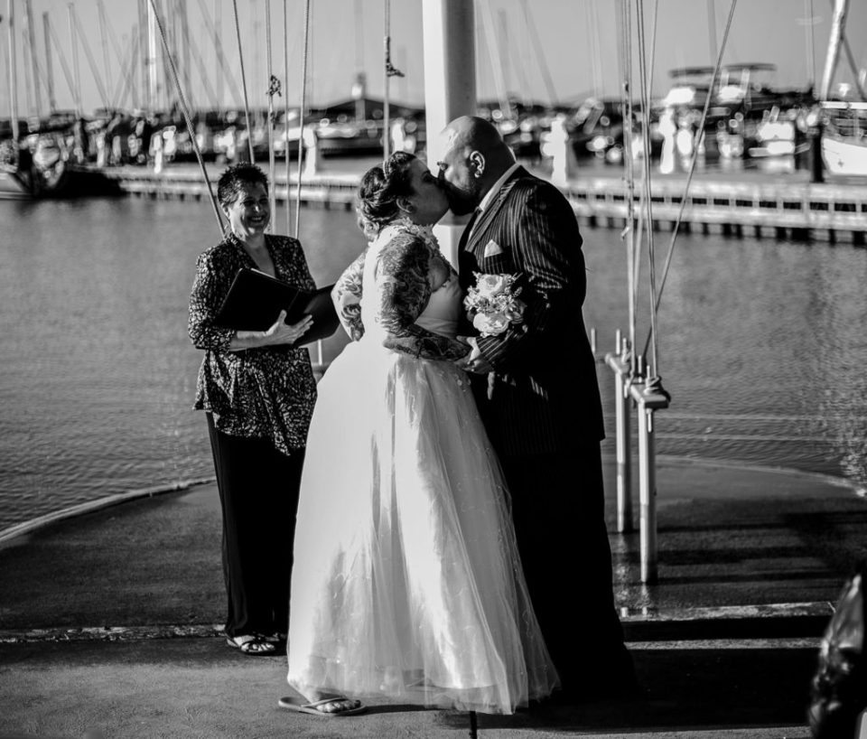 Bride and groom share first kiss at their Erie Yacht Club wedding