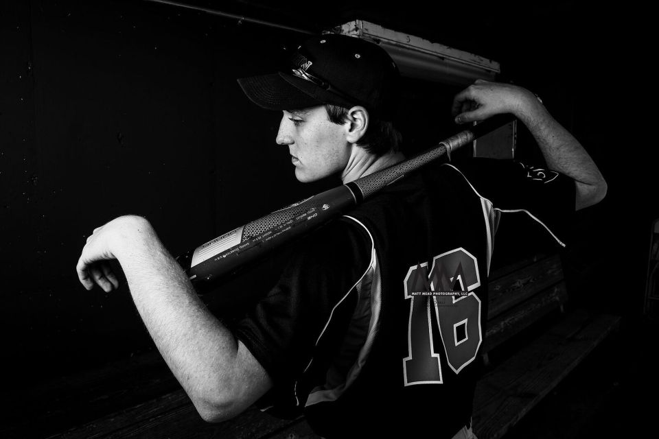 black and white photo of teen resting baseball bat on his shoulders for Erie PA senior portrait session