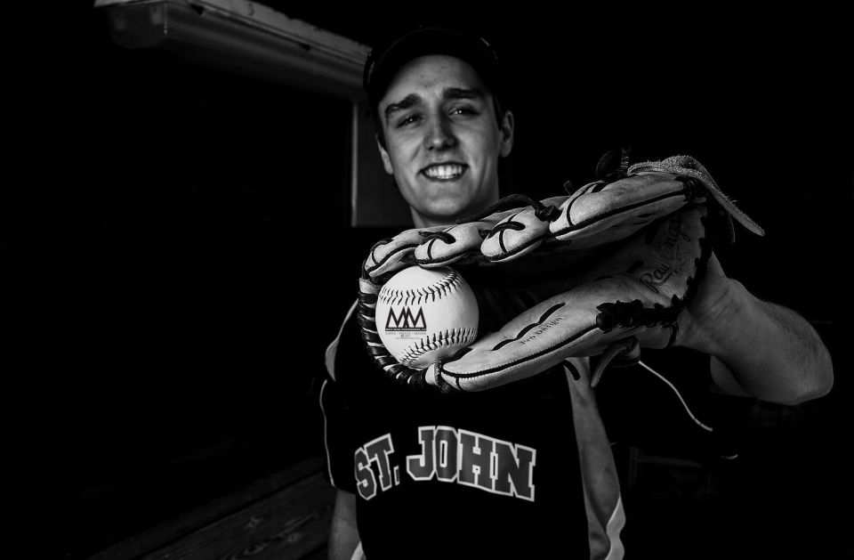 teen holding baseball in glove for Erie PA senior portrait session