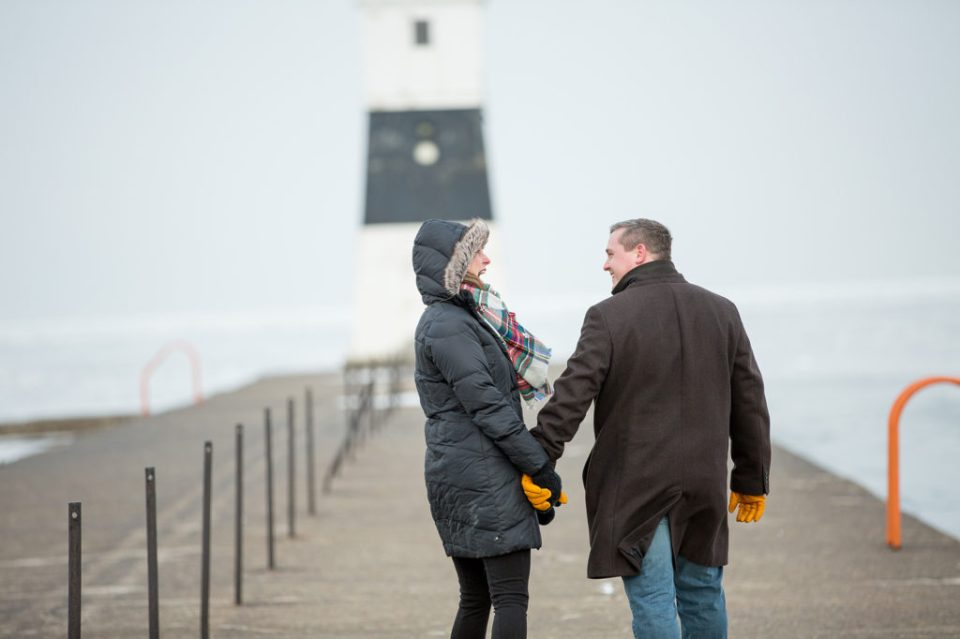 engaged couple walking on North Pier during Lake Erie engagement session in Erie, PA