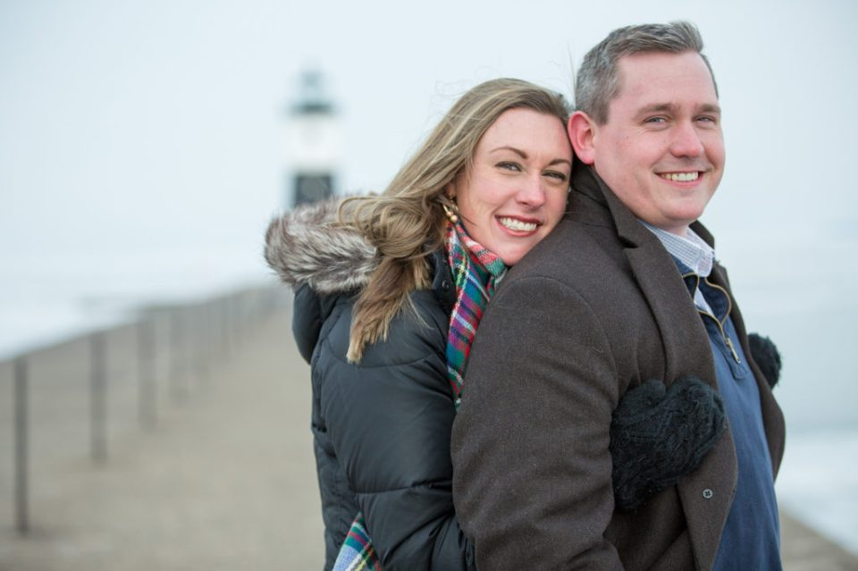 engaged couple embrace at North Pier Lighthouse during Lake Erie engagement session