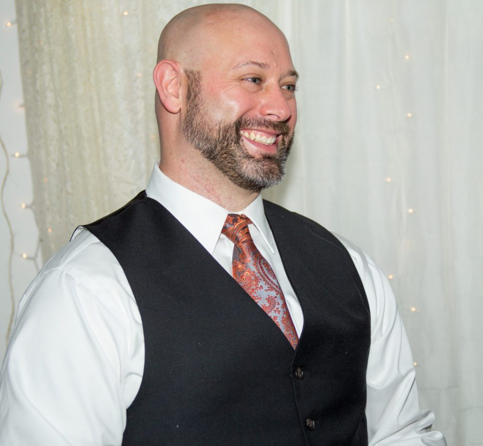 groom smiling as he listens to bride's written vows in Erie, PA