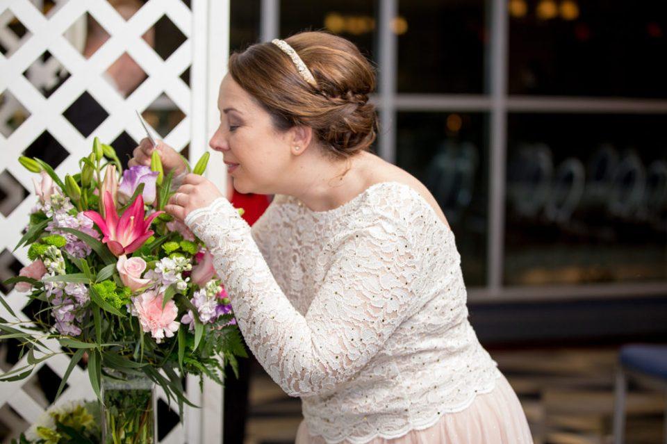 bride smelling flower arrangement at Sheraton Bayfront hotel wedding in Erie, PA