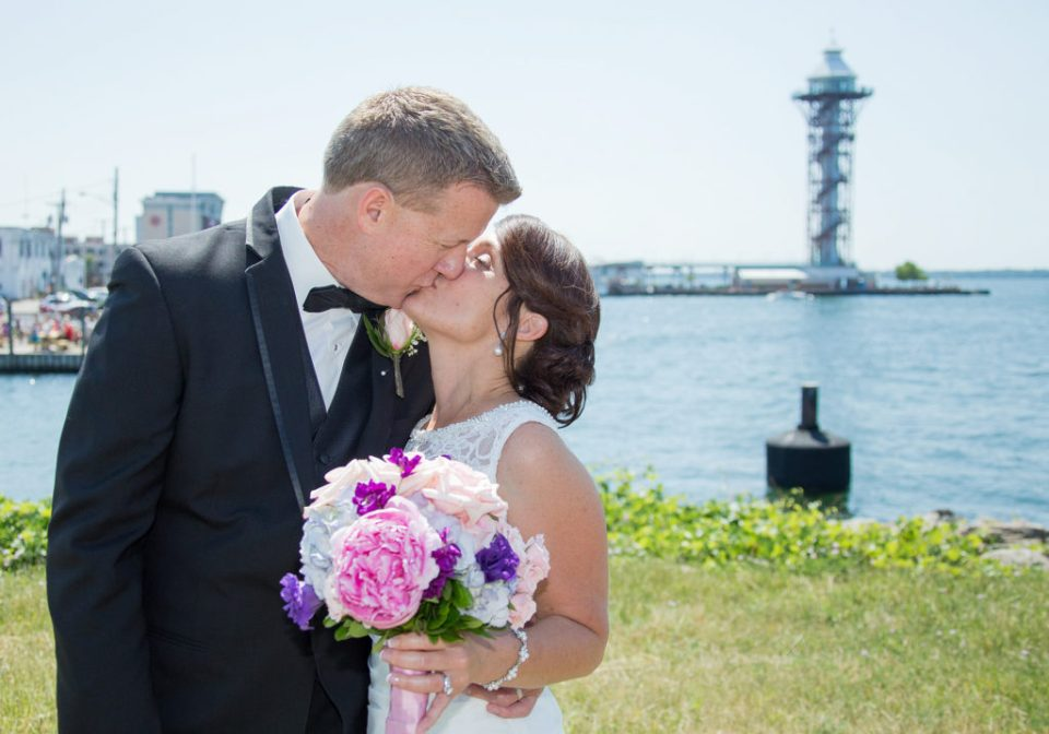 bride and groom kissing in front of Bicentennial Tower in Erie, PA