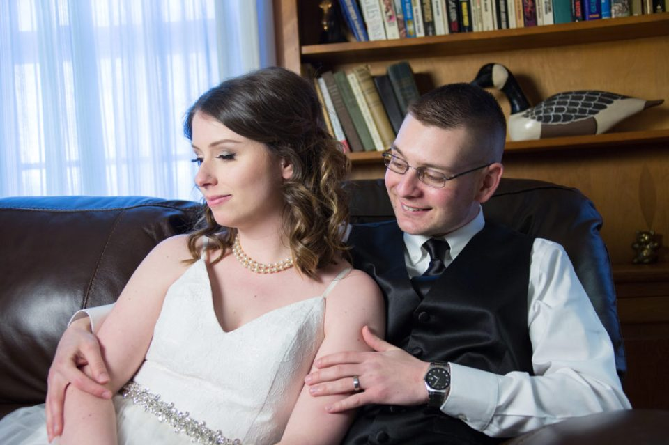 bride and groom relaxing on a sofa during wedding portrait session at the Barn at Conneaut Creek