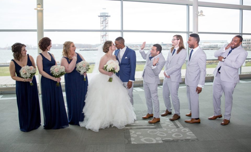 bride and groom kiss while wedding party looks on in shock at Sheraton Bayfront Hotel Erie, PA