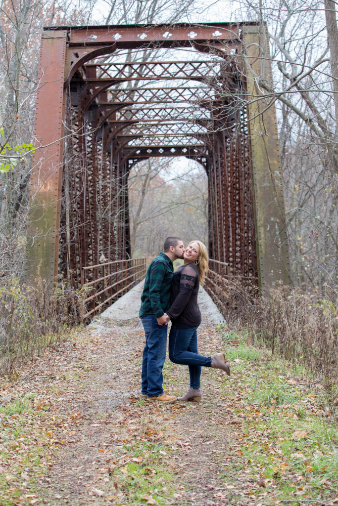 couple stands in front of old railroad bridge at the Barn at Conneaut Creek