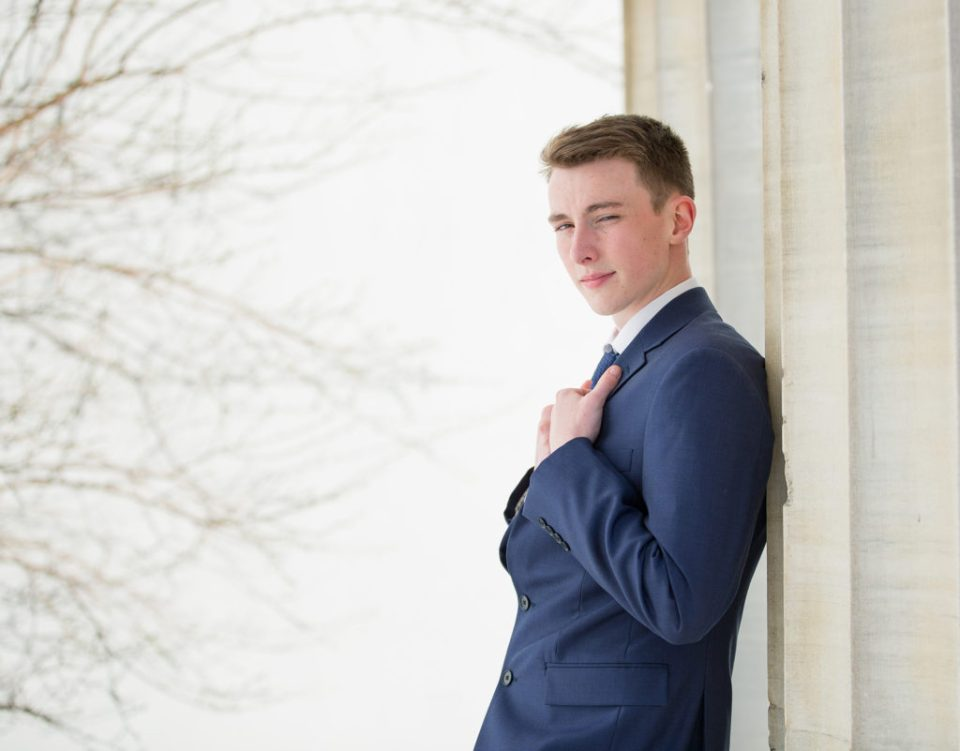 young man leaning against columns of Erie Art Museum for downtown Erie senior portrait session