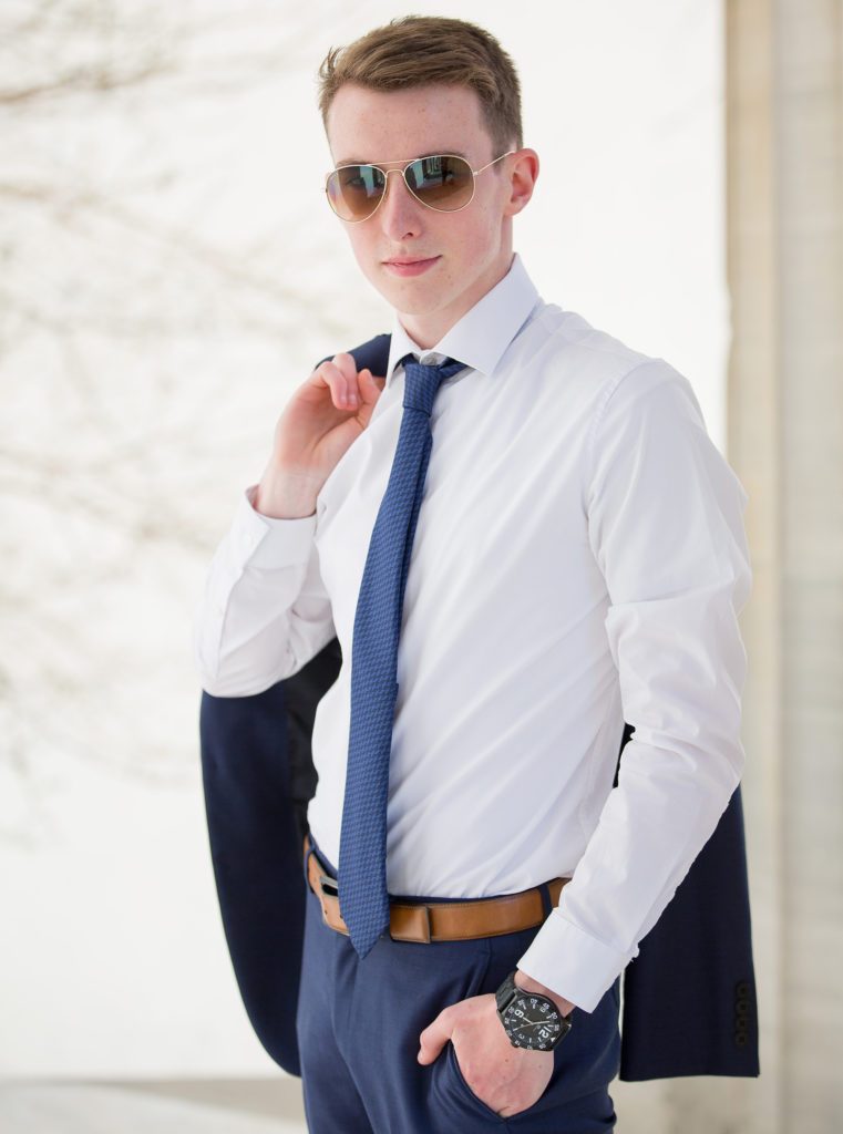 young man wears sunglasses with suit jacket over his shoulder for downtown Erie senior portrait session