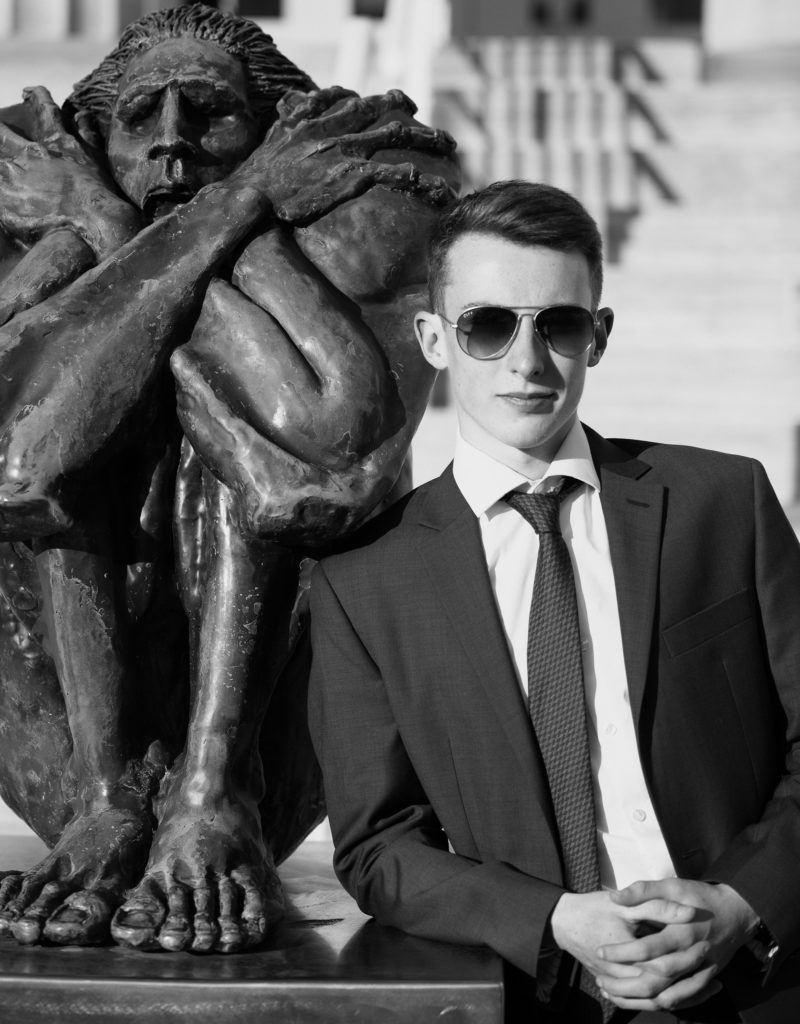 Young man wearing sunglasses leans against the statue outside of Erie Art Museum for downtown Erie senior portrait session