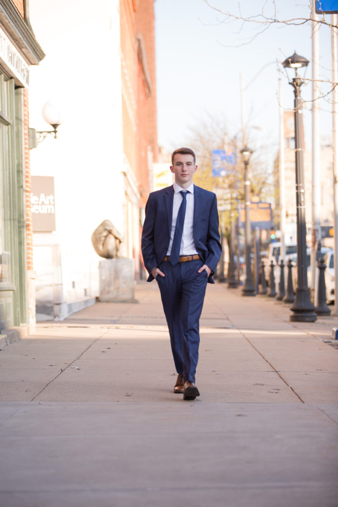 Young man in navy blue suit walks toward camera in downtown Erie senior portrait session