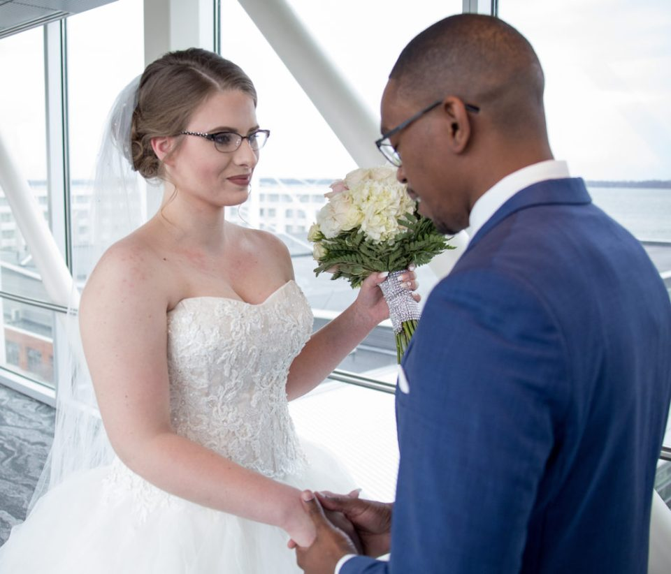 Erie, PA bride and groom holding hands during first look photo at Sheraton Bayfront Hotel