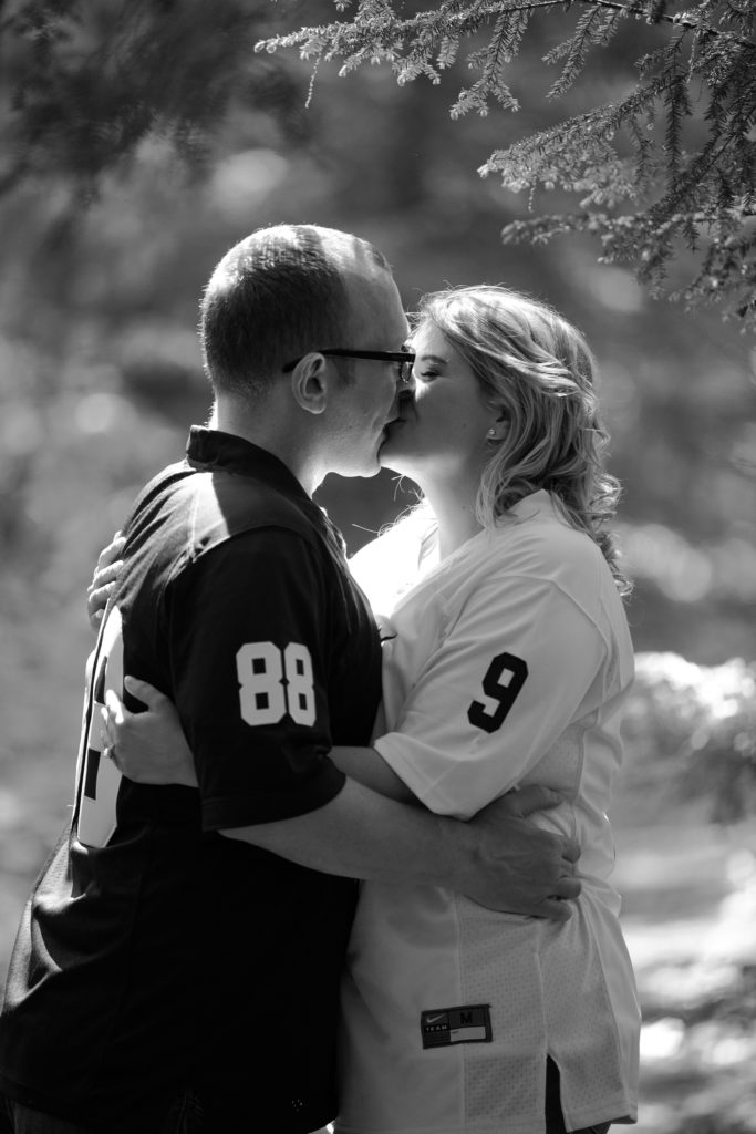 black and white portrait of couple kissing in the arboretum at Penn State Erie engagement session