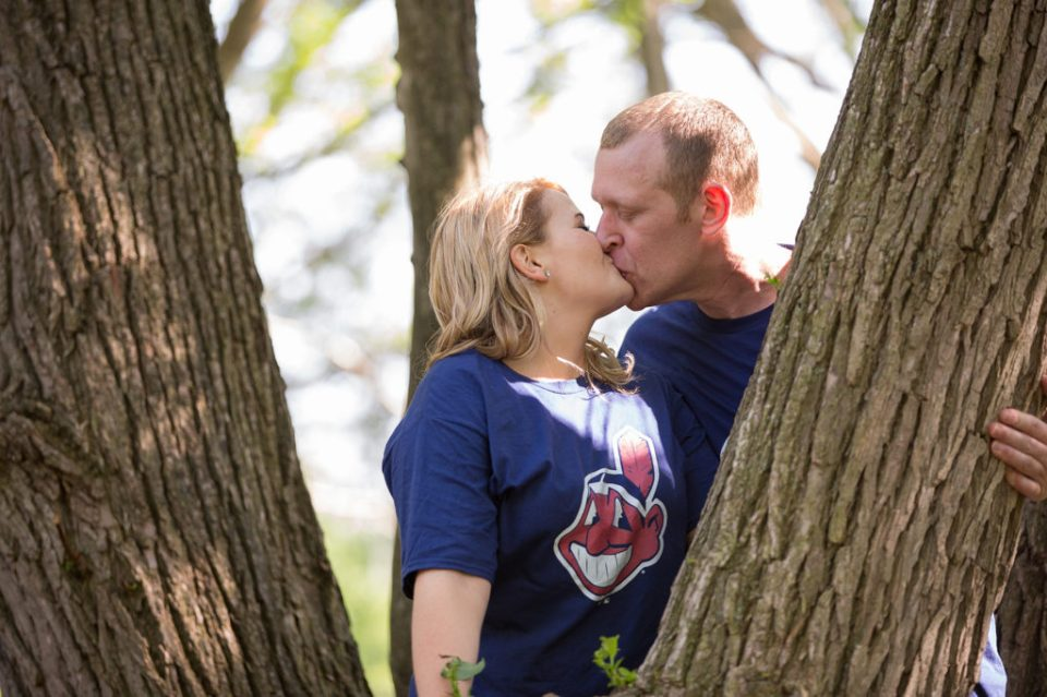Engaged couple kisses after climbing a tree in Frontier Park in Erie, PA