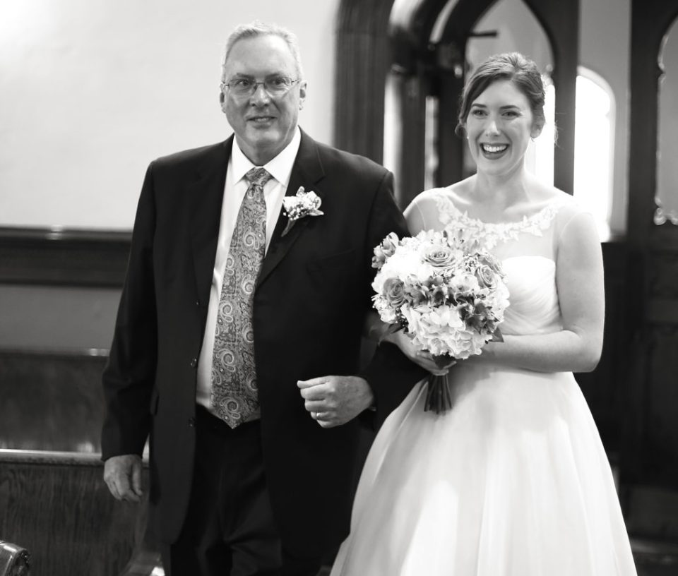 bride smiles as she walks down the aisle with her father