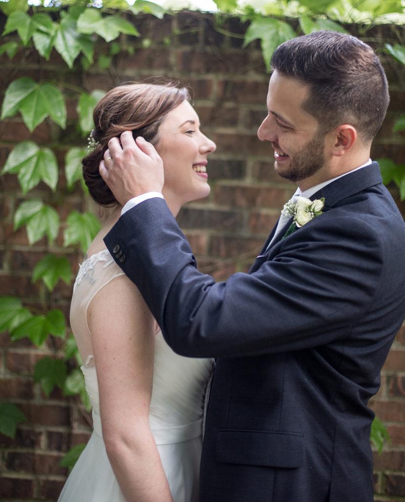 groom tucks bride's hair behind her ear at Pittsburgh National Aviary wedding