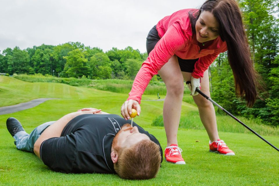 woman place golf tee in fiance's mouth as he lies on the ground at Whispering Woods golf course in Erie, PA