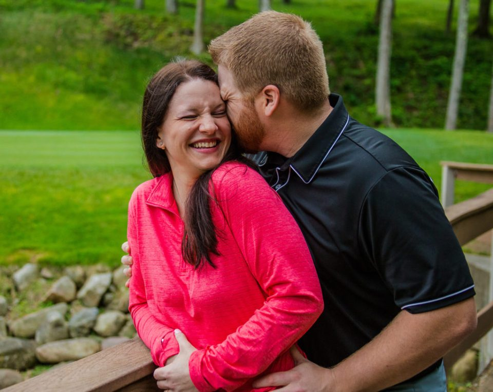 man whispers in woman's ear during Whispering Woods engagement photos