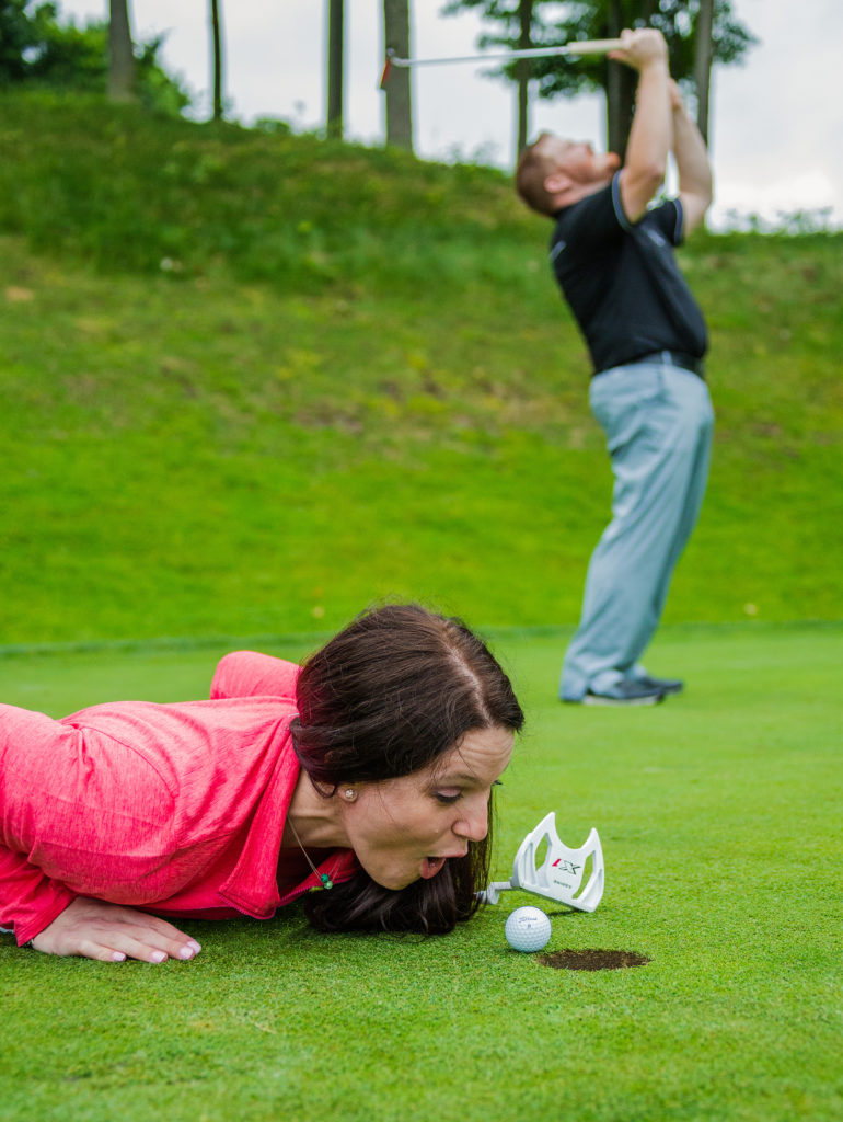 Woman tries to help golf ball into the hole at Whispering Woods golf course in Erie, PA