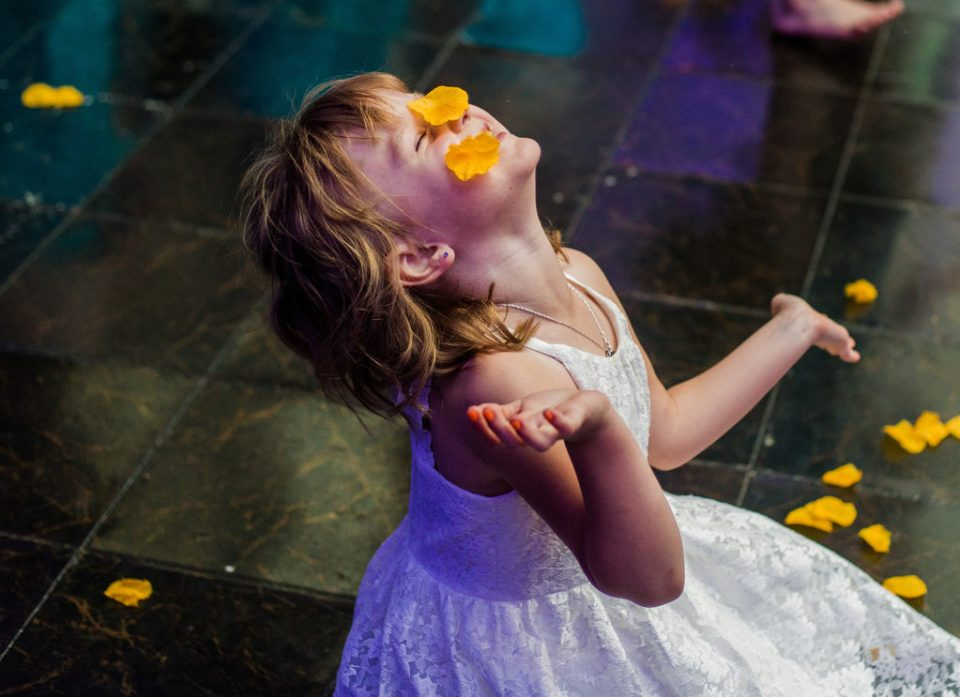 child sits on the floor and throws flower petals in Erie PA