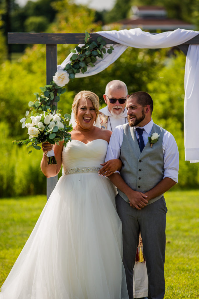 bride and groom walking together at the end of their Edinboro University wedding