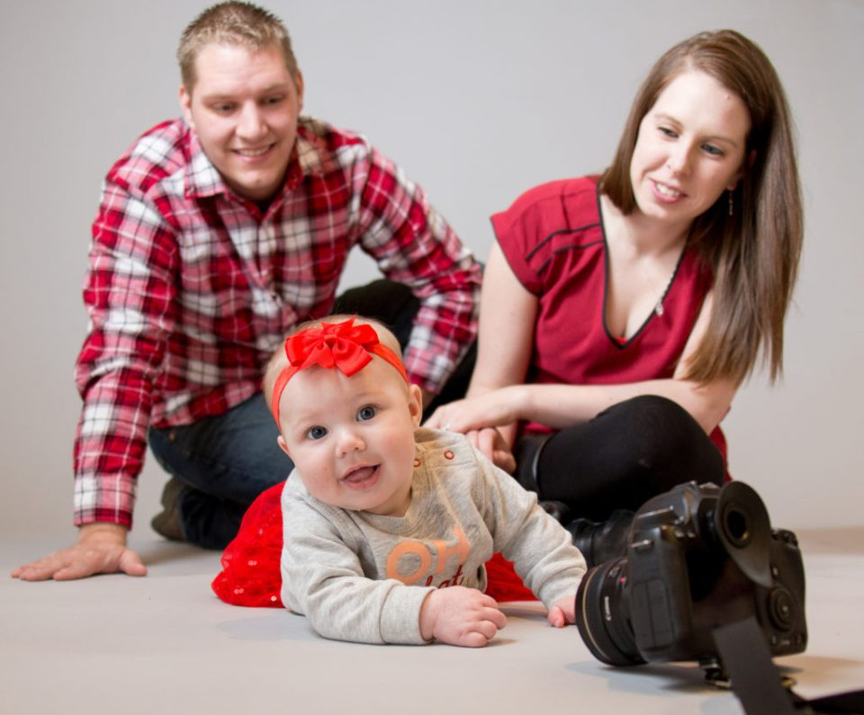 Mother and father pose with baby for family portrait session in Erie, PA