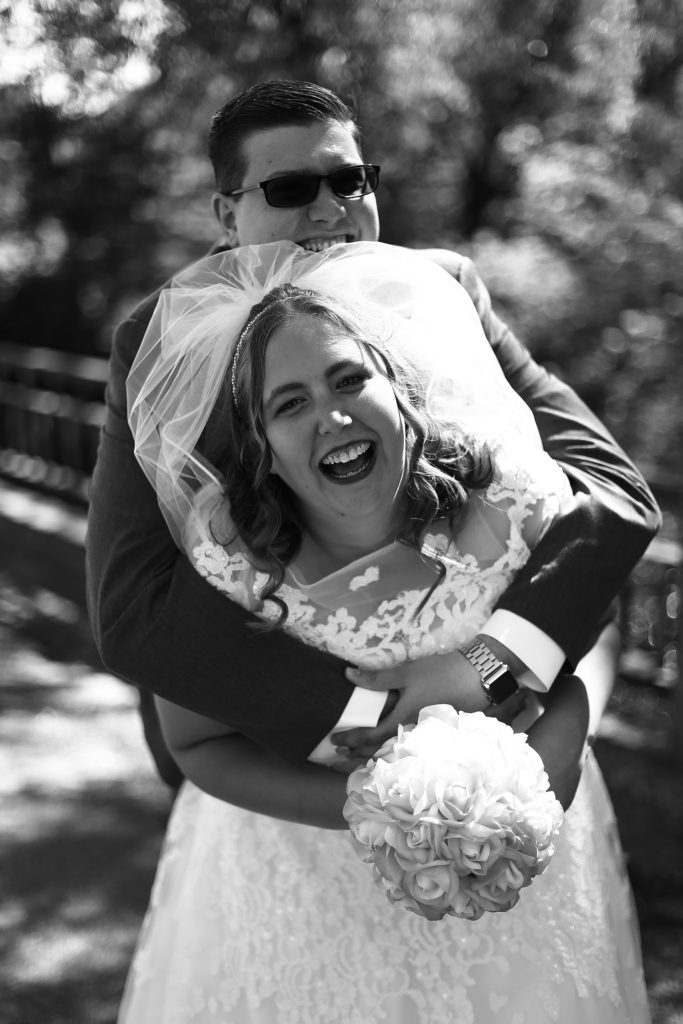bride and groom laughing together after small town wedding at Torpedo Community Church
