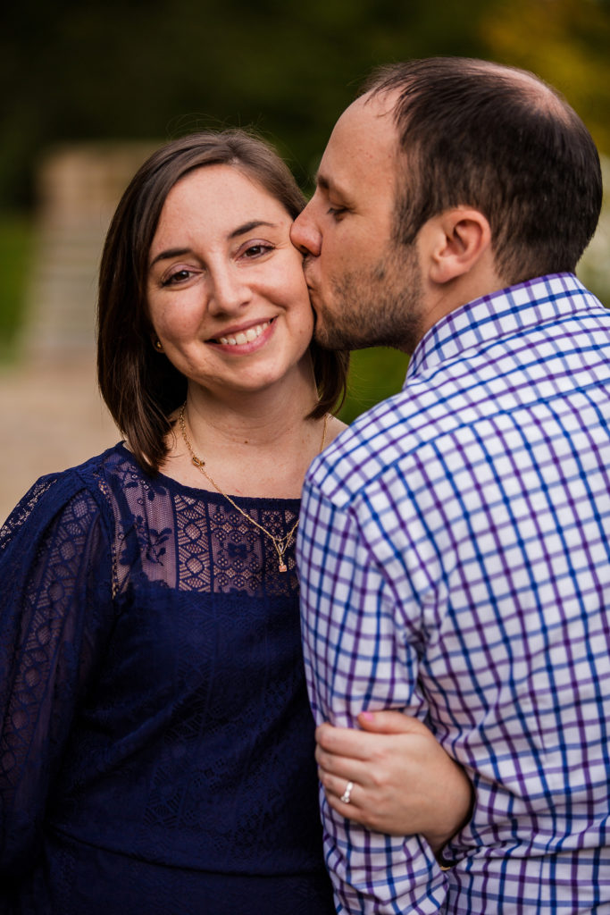 Man kisses fiancee on the cheek whi;e walking through Mellon Park in Pittsburgh PA