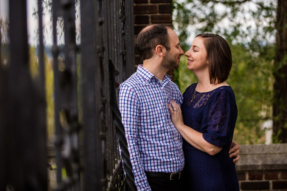 Engaged couple smile together against an iron fence at Mellon Park in Pittsburgh PA