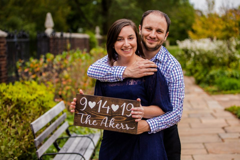 Engaged couple poses with a handmade sign announcing their wedding date in Mellon Park